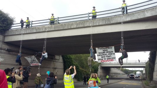 Nonviolent protesters block arms fair traffic by climbing down from the bridge near DSEI